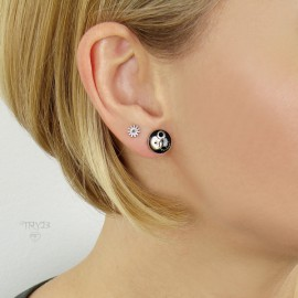 Black ear studs of silver and cogs.