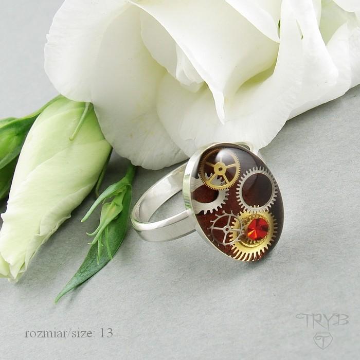 Srebrny pierścionek o owalnym bordowym oczku z trybami z zegarków