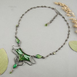 A dragonfly necklace of oxidized silver with peridots.