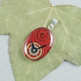 Sterling silver pendant with watch parts composition on a  red background.